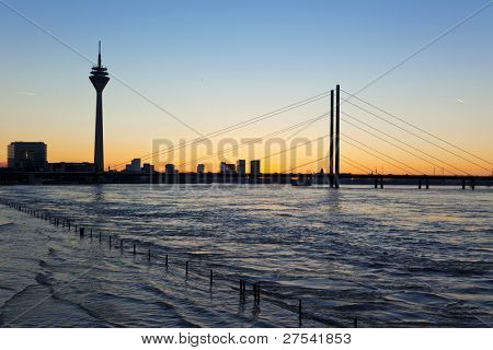 skyline of Dusseldorf at sunset during high tide of the River Rhine