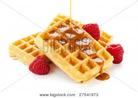 caramel sauce flowing over a heap of belgian waffles decorated with raspberries, isolated on white background
