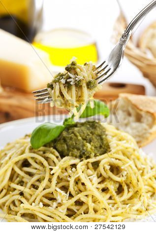 silver fork with spaghetti alla genovese above full plate