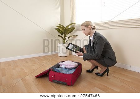 Businesswoman looking at family portrait while preparing her baggage for a businesstrip
