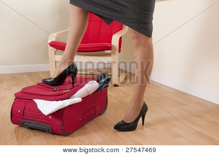 Businesswoman trying to close her suitcase