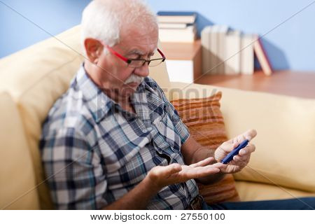 Senior man doing blood sugar test at home