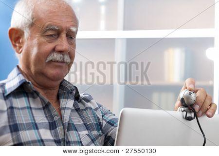 Senior man/Grandfather speaking through webcam