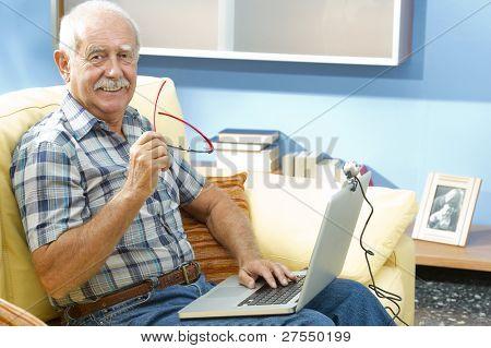 Smiling senior man working at home
