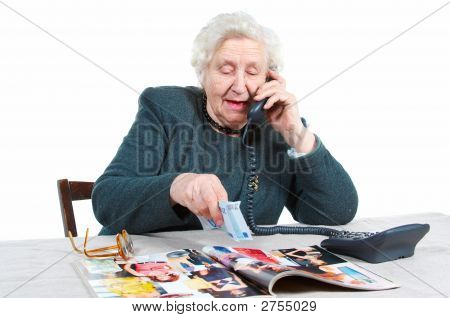 Grandmother Is Watching Catalogue And Making An Order.