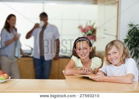 gleichgeordneten Tablet in der Küche mit ihren Eltern dahinter