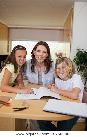 Siblings getting help with homework from their mother