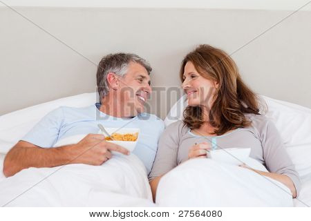 Happy mature couple eating cereals in bed