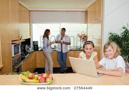 Kinder mit ihrem Notebook in der Küche und Eltern dahinter