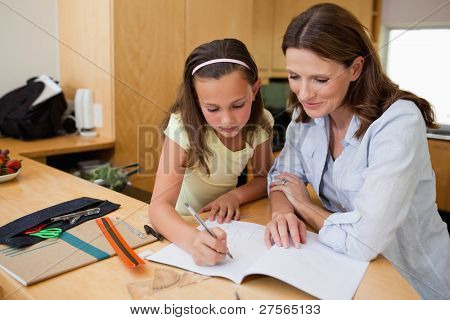 Girl doing homework together with her mother