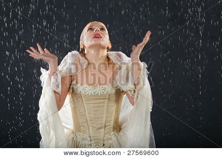 beautiful girl wearing in dress with corset freezes in rain and catches drops by hands
