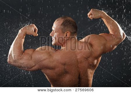 Undressed bodybuilder stands in rain back to camera and shows muscles.
