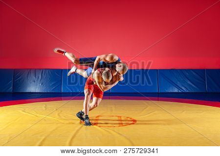 poster of Two Young Men In Blue And Red Wrestling Tights Are Wrestlng And Making A Hip Throw On A Yellow Wrest