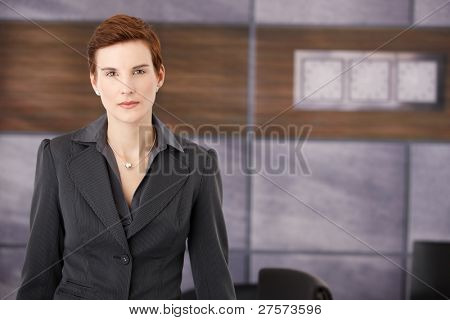 Determined smart businesswoman standing in office, looking at camera.?
