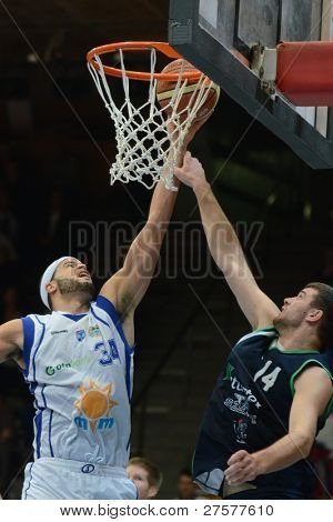 KAPOSVAR, HUNGARY - DECEMBER 10: Michael Fey (in white) in action at a Hungarian Championship basketball game Kaposvar (white) vs. Szeged (blue) on December 10, 2011 in Kaposvar, Hungary.