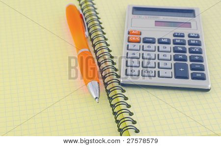 Digital Calculator And Orange Pen On The Yellow Writing-book
