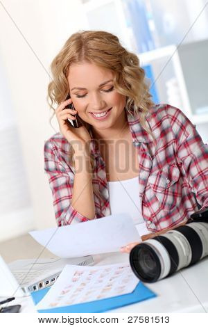 Beautiful photographer looking at story board for photo session
