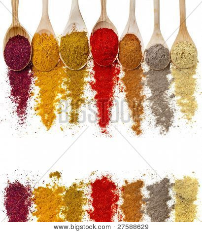 border frame of powder spices on spoons isolated on a white background