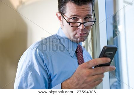 Serious male business executive sending text message on mobile phone