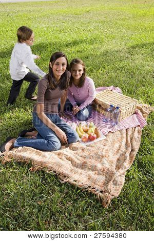 Little boy and two sisters having picnic in park