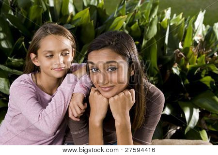 Pretty mixed-race Indian teen girl smiling with 10 year old sister leaning on shoulder