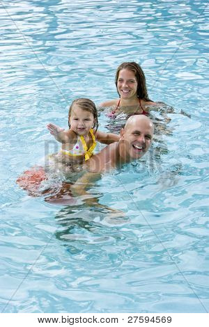 Family with 2 year old girl playing in swimming pool