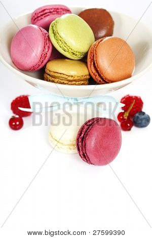 Colorful macaroons in a white plate and fresh berries