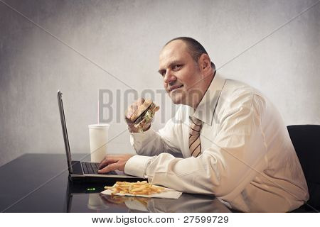 Fat businessman at the office eating junk food