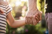 Hands Of Kid And Old Man With Blurred Foliage On Background poster