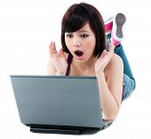 image of asian woman  - Portrait of a young Asian woman looking amazed at laptop over white background - JPG