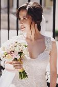 Gorgeous Bride In Amazing Gown  Holding Wedding Bouquet And Posing In Sunny City Street At Old Build poster