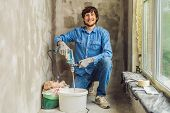 Young Male Painter Kneads Putty With Water In A Bucket Using A Hand-held Mixer For Building Mixes poster