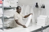 An African Male Hotel Worker Folds A Clean White Towel. Hotel Staff Workers. Hotel Linen Cleaning Se poster