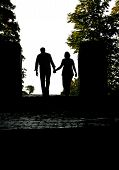 stock photo of walking away  - silhouette of a happy couple walking away holding hands - JPG