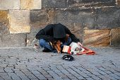 Homeless Hooded Man, Head Down And His Dog On The Cobblestones