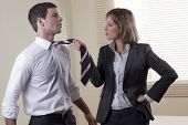 Business woman pulling his colleague from necktie