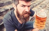 Man With Beard And Mustache Holds Glass With Beer While Sits On Stone Stairs, Defocused. Guy Raising poster