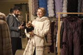 Customer With Beard And Woman Buy Furry Coat. Fashion And Shopping Concept. Couple In Love Tries Exp poster