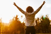 Rear View Shot Of Happy Young Man Rising Hands Up Standing In The Park Enjoying Beautiful Sunset Vie poster