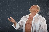 Tanned bodybuilder wearing white wet shirt stands in rain and catches drops by hand and mouth.