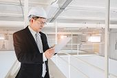 Asian Executive Engineer In White Helmet Using Tablet In Industrial Factory, Concept For Executive E poster