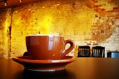 stock photo of coffee cups  - Cappuccino coffee cup and saucer in a funky interior - JPG