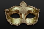 picture of mummer  - clouse up of a golden mask over a dark background