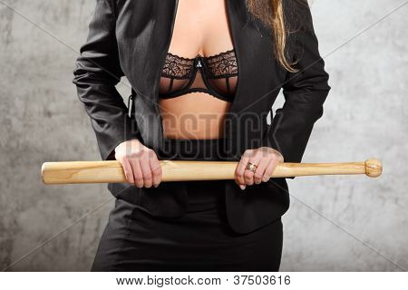 Woman in unfastened business suit in bra hold bat, half body