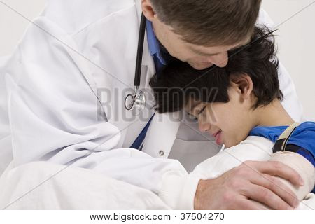Doctor comforting little patient in arms