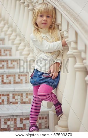 Girl 3 years old in a denim skirt and pink tights is a beautiful staircase
