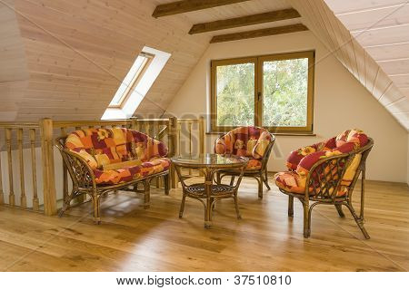 Attic Room With Garden Furniture. Walls Covered With Timber Planks, Beams In The Ceiling.