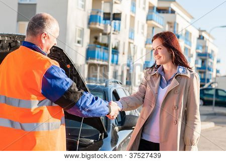 Woman greeting mechanic after her car breakdown problem man technician