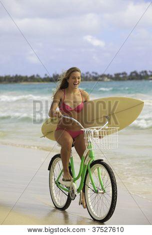 girl on bike with surfboard