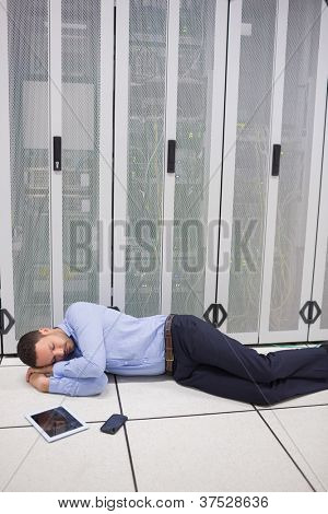 Technician sleeping in front of servers in data  center